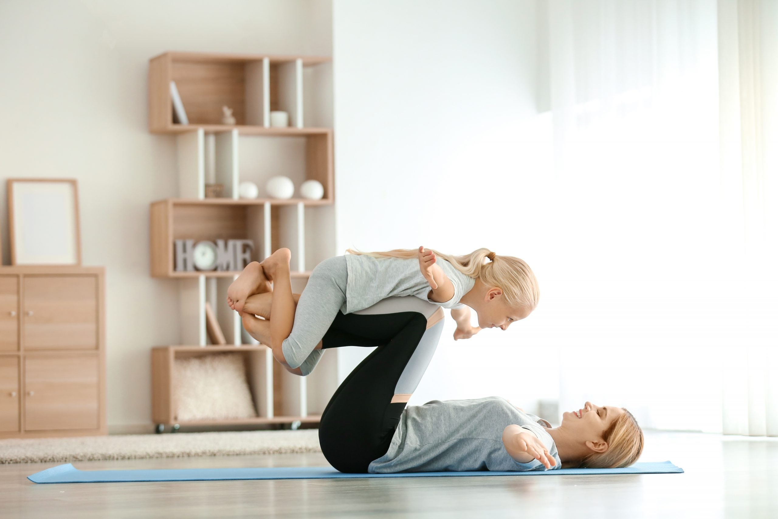 Mother with little girl doing yoga at home